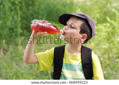 Child boy drinking from a plastic bottle on a outdoor trip.