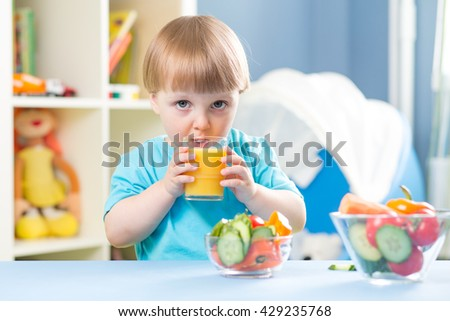 child boy drinking juice from glass indoors