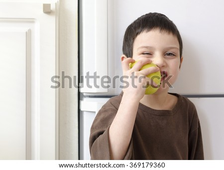 Child boy eating a green apple at home in the kitchen. - stock photo