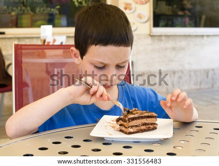 Child boy eating a slice of chocolate cake in a street cafe