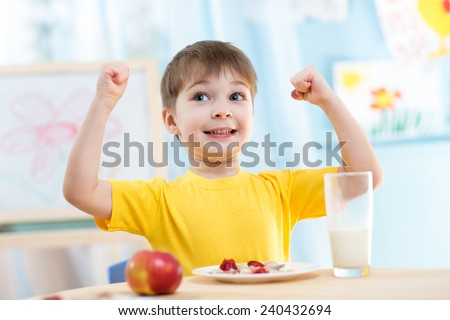 child boy eating healthy food and showing his strength indoors - stock photo