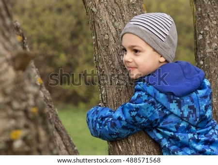 Child boy hugging and climbing a tree in a park or garden.
