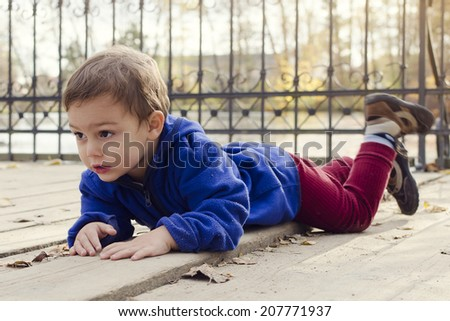 Child boy laying on a wooden floor ground on a bridge or landing in autumn or fall park outside.