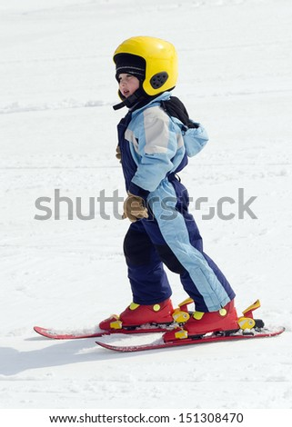 Child boy learning  skiing  on slope in winter ski resort.