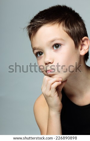 Child boy looking to the side on grey background - stock photo