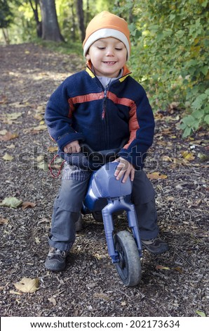 Child boy on a toy bike on a path in park or forest at autumn or fall.  - stock photo