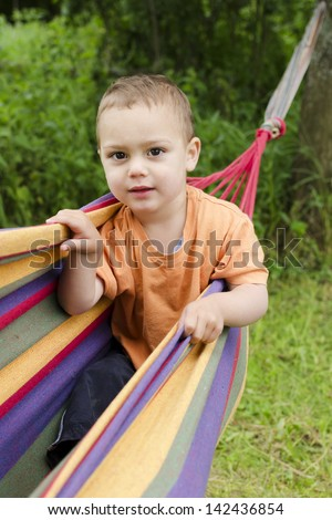 Child boy playing in a colorful hammock in a garden.