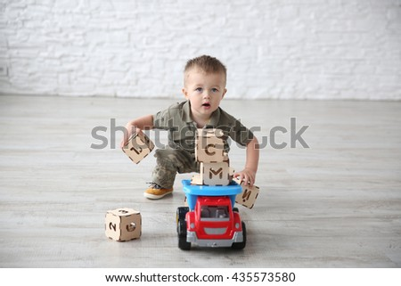 Child boy playing in the room with toy cars and wooden letter toy blocks