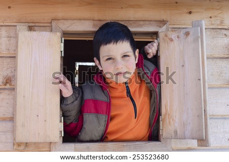 Child boy playing in wooden playhouse, looking from open window - stock photo