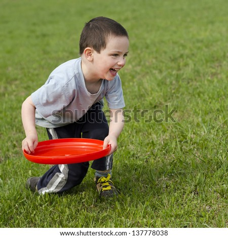 Child boy playing on a grass with a red frisbee disk. - stock photo