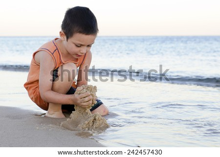 Child boy playing with wet sand on a beach at the edge of shallow water. - stock photo