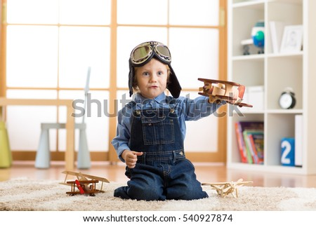 Child boy pretending to be pilot aviator. Kid playing with toy airplanes at home. Travel and dream concept