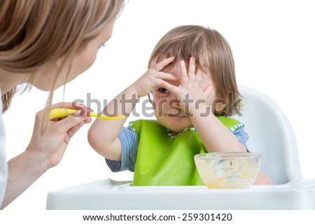 Child boy refuses to eat closing face by hands, isolated on white - stock photo