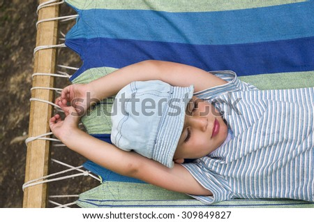 Child boy resting or sleeping in hammock in summer garden