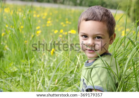 Child boy sitting in a long grass on meadow with dandelions