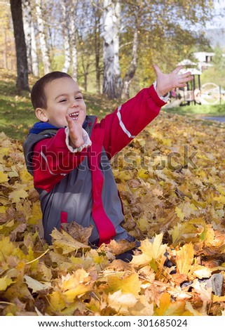 Child boy sitting on ground, playing with yellow  leaves in autumn or fall. - stock photo