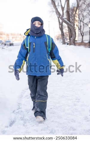 Child boy throwing snow in an open field of snow during a frigid Canadian Winter - stock photo