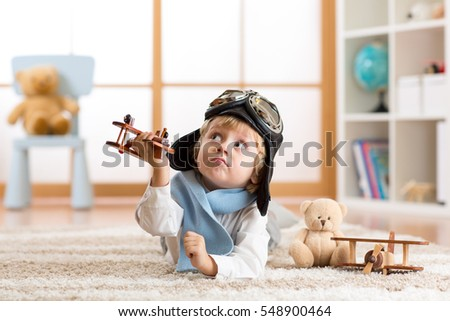 Child boy toddler playing with toy airplane and dreaming of becoming a pilot