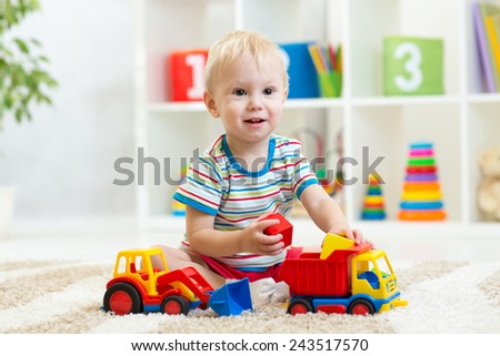 child boy toddler playing with toy car - stock photo
