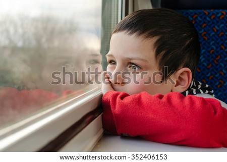 Child boy traveling by and looking from a window.