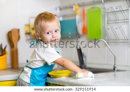 Child boy washing dishes in a domestic kitchen - stock photo