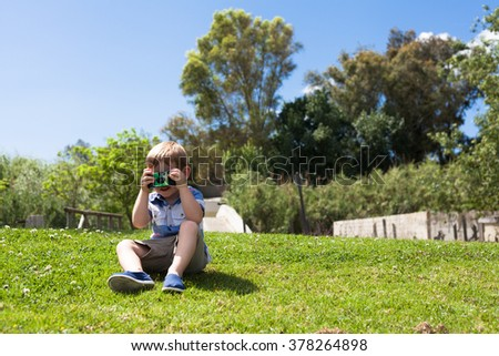 Child boy with camera outdoors taking his first photo while sitting in the grass and enjoying sunny day in nature.