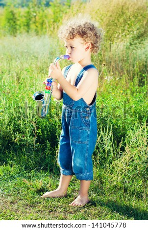Child boy with saxophone outdoors. Musician. Conceptual idea.