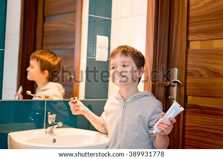 Child brushing his teeth in the bathroom. Holds toothpaste  in left hand. Dressed in grey hooded blouse - stock photo