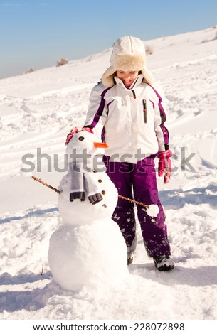 Child building a snowman - stock photo