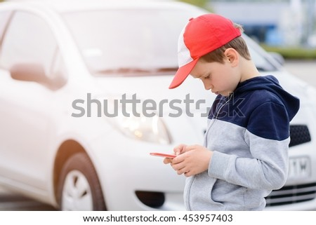 Child busy playing the smartphone mobile games does not pay attention to the moving car. Boy child playing mobile games on smartphone on the street