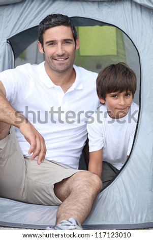 Child camping with his father - stock photo