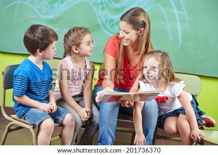 Child care worker and children reading a picture book together in a kindergarten