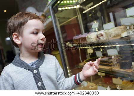 Child choosing a cake in the cafe - stock photo