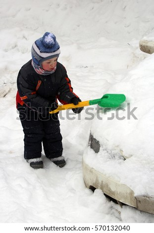 child cleans a car from the snow shovel