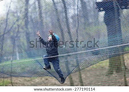 Child climbing into a net at outdoor playground - stock photo