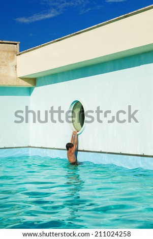 child climbs on the edge of the pool, outdoor - stock photo