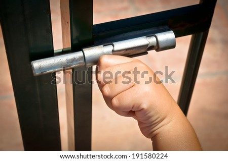 child closing a latch - stock photo
