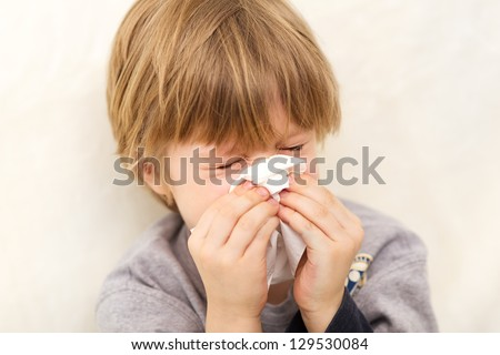 Child cold flu illness tissue blowing runny nose - stock photo