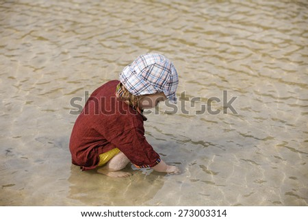 Child collecting pebbles and shells on a tropical sandy beach in the summer. Carefree, playful childhood concept.  - stock photo