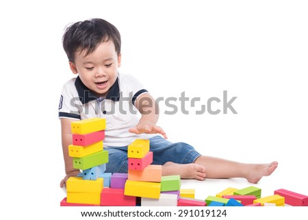 Child collects a pyramid. Asian child builds a tower of cubes - stock photo
