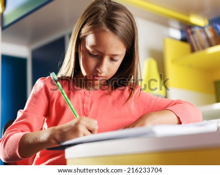 child concentrating on homework in bedroom - stock photo