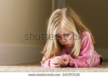Child could be sad due to abuse, domestic violence, or even sad due to a bully - stock photo
