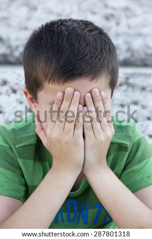 child covering face with hands - stock photo