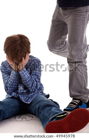 child crying on the floor being kicked by a teenager