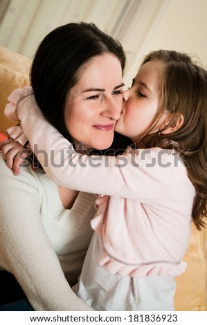 Child (cute girl) kissing her mother - indoors at home