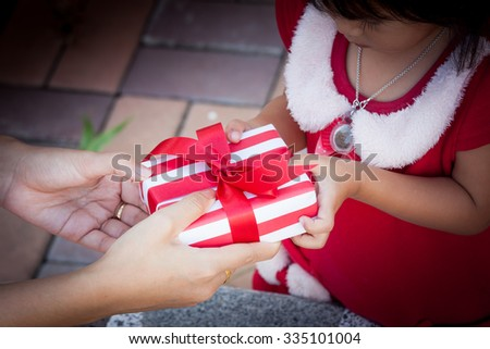 Child cute little girl receiving christmas present from young woman in dark tone - stock photo