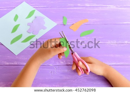 Child cuts a leaf from green paper. Kid holds scissors in his hands. Details to create a card. Child doing crafts from colored paper. Art project for kindergarten, summer camps. Tutorial. Step - stock photo