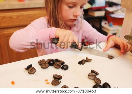child cutting olives - stock photo