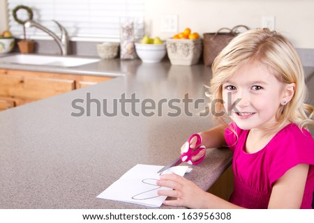 Child cutting out paper with scissors, sitting at table in kitchen at home. - stock photo