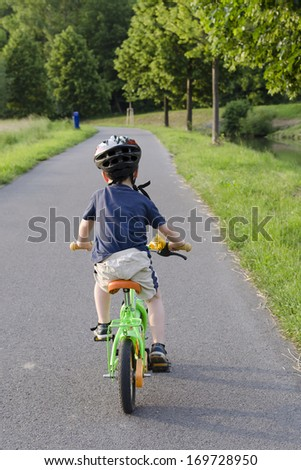 Child cycling on a cycle path in nature, back view. - stock photo